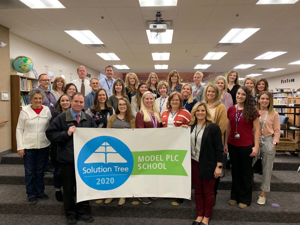Staff standing with banner that says Solution Tree 2020 Model PLC School